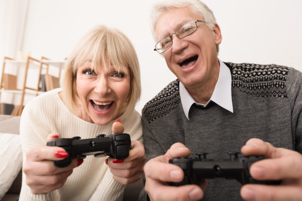 Senior couple playing video games together at home