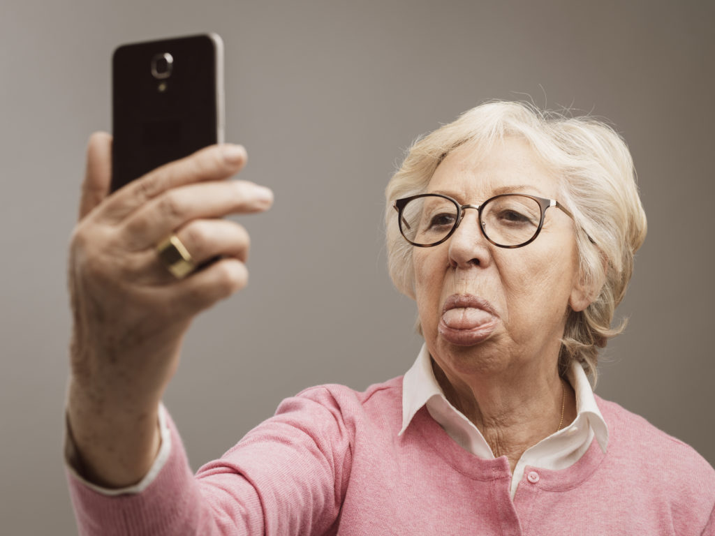 Funny senior lady taking selfies with tongue out using her smartphone