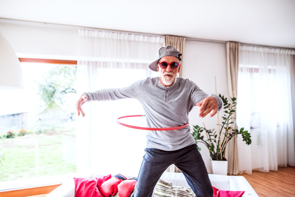 Older man hula-hooping at home!